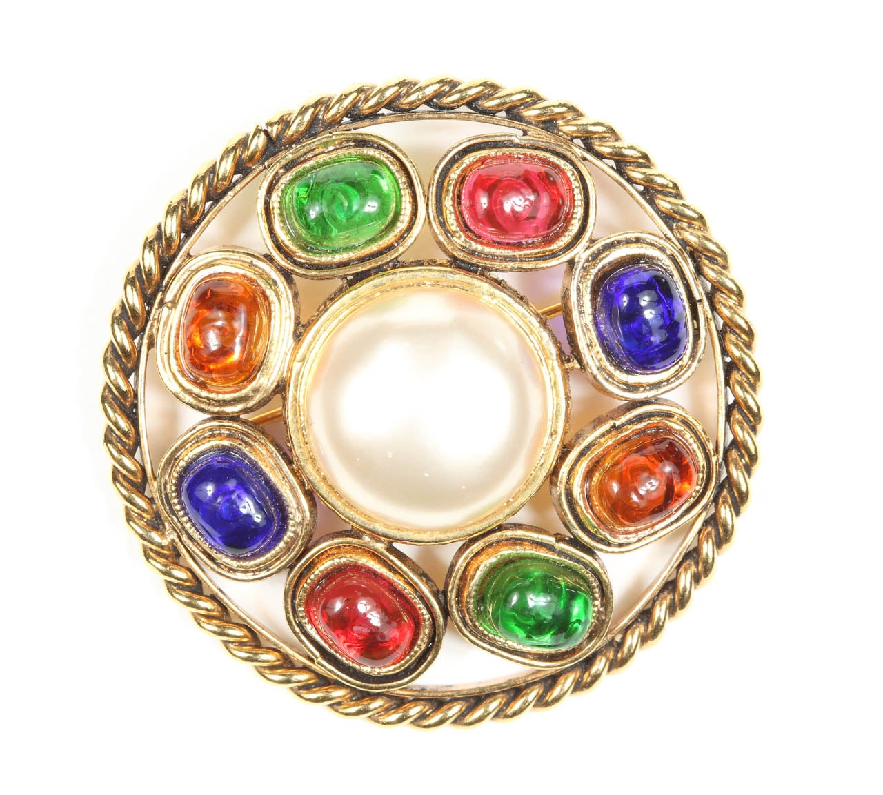 "A colorful Chanel brooch with a ring of colorful poured glass cabochons around a central glass pearl and framed in a gilt metal rope. Marked on the back with the ""Chanel Made in France"" oval cartouche indicating that this is from collection 23,"