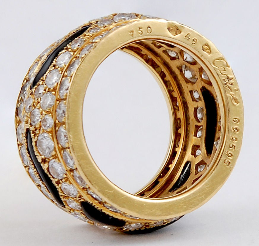 A vintage Cartier diamond band ring in 18k gold, designed in the 'Panthere' motif with polished onyx striped accents amongst collection quality brilliant-cut diamonds. Size 4 1/2.  Signed Cartier and numbered, with French assay marks.