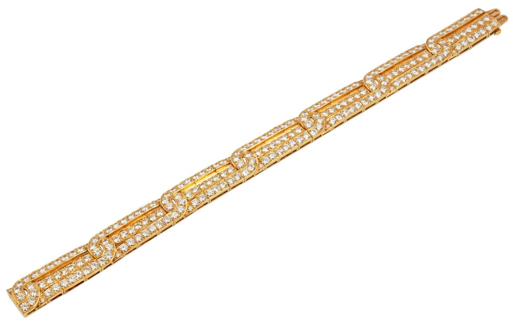 An elegant Van Cleef & Arpels gold and diamond bracelet in 18k gold; composed of three interlocking rows of 203 round diamonds weighing approximately 15 carats. Measuring 7 inches long.  Signed Van Cleef & Arpels and nubered, with French