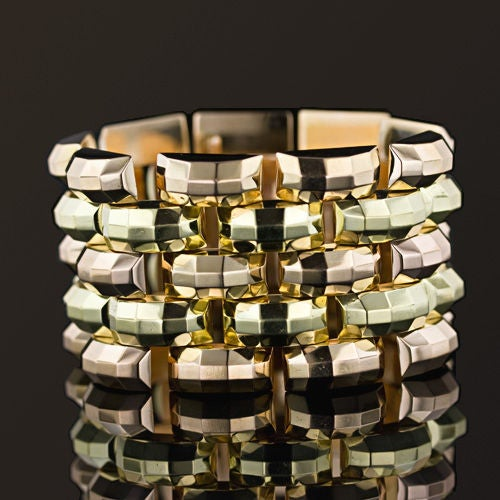 A bold and striking dual color gold (rose and green) 1 5/8 inch wide bracelet from the glamorous 1940's. Five alternating rows of glistening rose and green gold of a classic tank tread design distinguishes this exceptional piece.