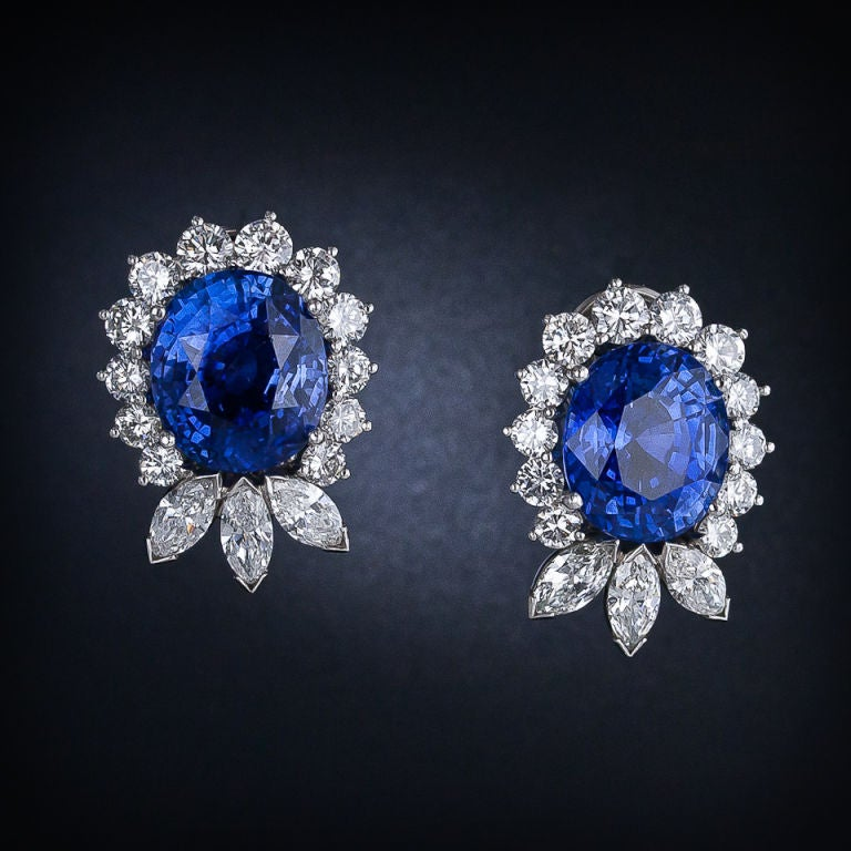A spectacular pair of entrancing, vibrant blue, oval sapphires are wreathed in a graduated row of bright white, round brilliant-cut diamonds transitioning into sparkling marquise diamond flames. Fabulous and classic ear clips - a fantasy in blue and