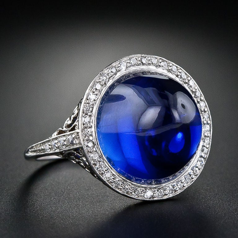 Phenomenal old gem material, transformed into a truly magnificent sugarloaf cabochon, is showcased in a sublime Edwardian mounting, circa 1900. This impressive, collectable and mesmerizing 15.75 carat natural sapphire is graced with a delicate halo