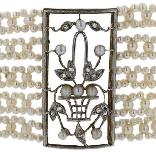 Three plaques adorned with flowing flower basket motifs are delicately rendered in platinum over gold and tiny twinkling rose-cut diamonds. The decorative plaques are connected by five rows of intricately strung natural seed pearls. A regal and