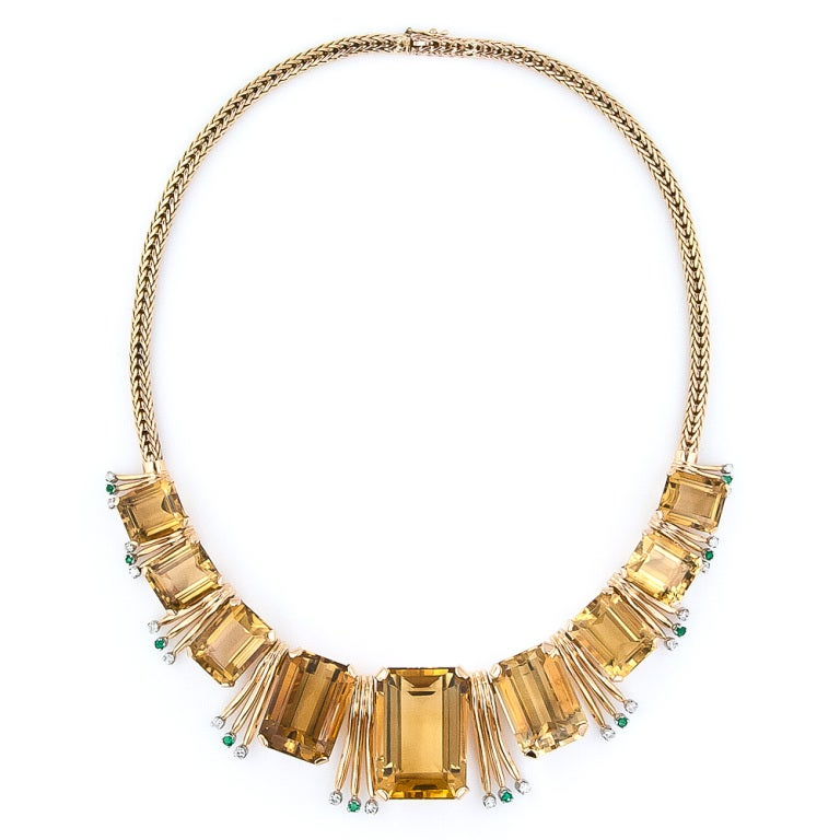 Nine graduated glowing golden citrines are punctuated by glistening emerald and diamond flares in this ultra-chic and stylish Retro necklace, artfully crafted in 18 karat rosy-yellow gold - circa 1940s-1950s. A mid-century beauty. 15 inches long, 9