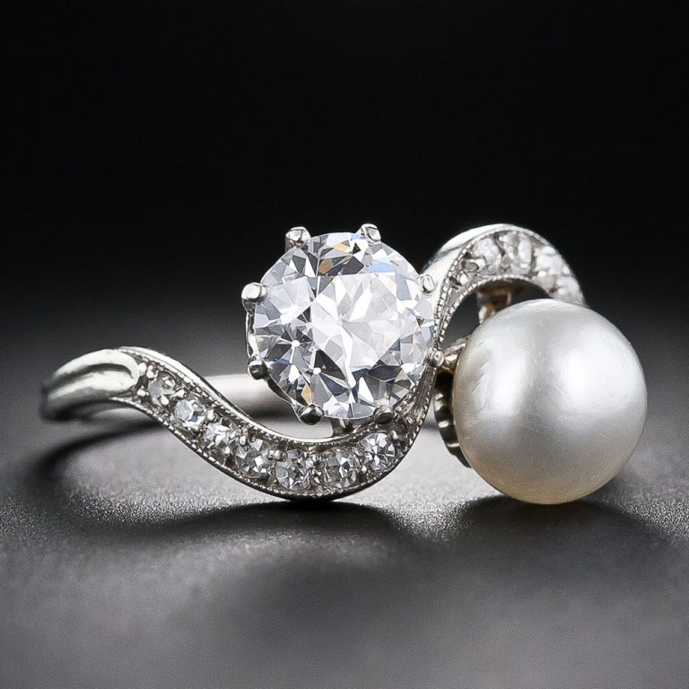 A sparkling, ice-white European-cut diamond, weighing 1.08 carats and a lustrous white natural pearl snuggle up together in this exquisitely beautiful Edwardian twin stone ring, delicately crafted in platinum - circa 1915. The diamond and pearl are