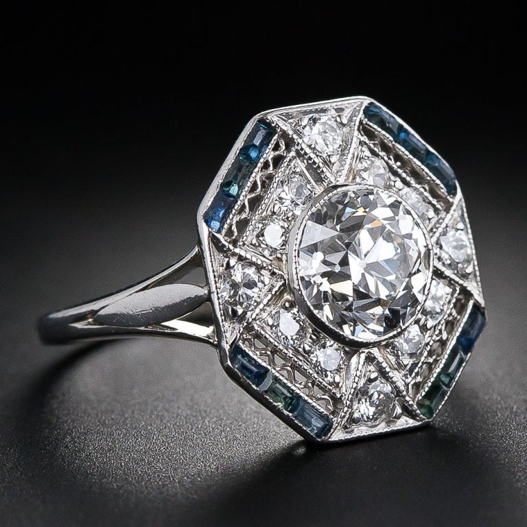 A strikingly beautiful Art Deco diamond ring featuring a bright-white and brilliant European-cut diamond weighing 1.28 carats. The center diamond is presented with consummate and sophisticated Art Deco geometry in a superlative hexagonal-shape