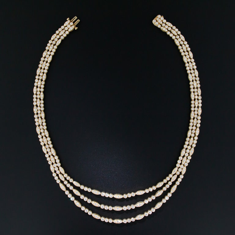 Cascading swags of glittering, bright-white, high-quality round brilliant cut diamonds, set in rich 18K yellow gold, drape over your decolletage in this stunning and sexy three-in-one necklace by the justly celebrated American jeweler - Oscar Heyman