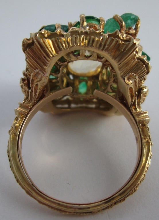 of floral design set centrally with a yellow sapphire, in an openwork and engraved emerald surround;