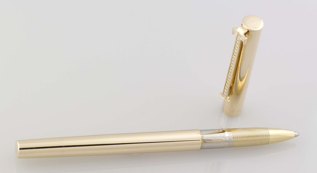 """Elegant and collectible 14K yellow gold and diamond """"T clip"""" roller ball pen from Tiffany & Co. It features a clip shaped like the letter """"T"""", embedded with high-grade round cut diamonds.<br /> Hallmarks: Tiffany & Co., 14K."""