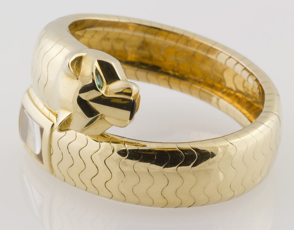 Impressive and very rare Cartier lady's 18k yellow gold flexible bangle watch from the Panther collection. It features the signature panther head at one end, with marquise cut emerald eyes and onyx nose. The other end features a gold tone watch dial