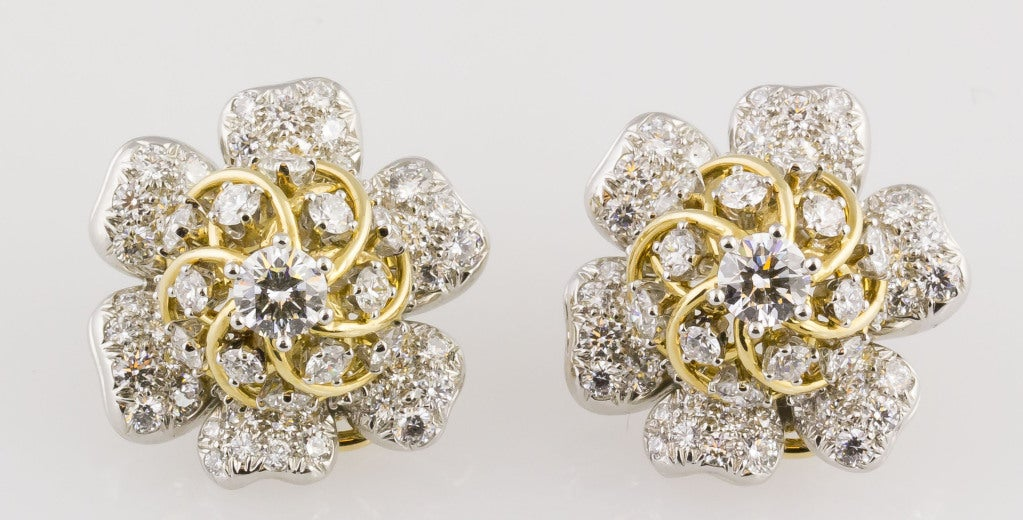 Chic diamond and platinum & 18K yellow gold earrings by Tiffany & Co., Schlumberger. Designed as flowers, they are adorned with very high quality round brilliant cut diamonds of approx. 7.0-8.0 carats in total,  and further accented with 18k yellow