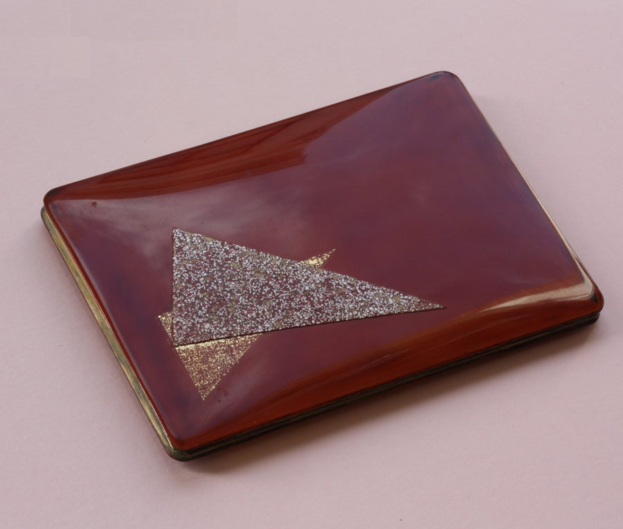A large metal box decorated with two triangle decorations in red and eggshell enamel on a brown back ground, signed: Jean Dunand, circa 1925.