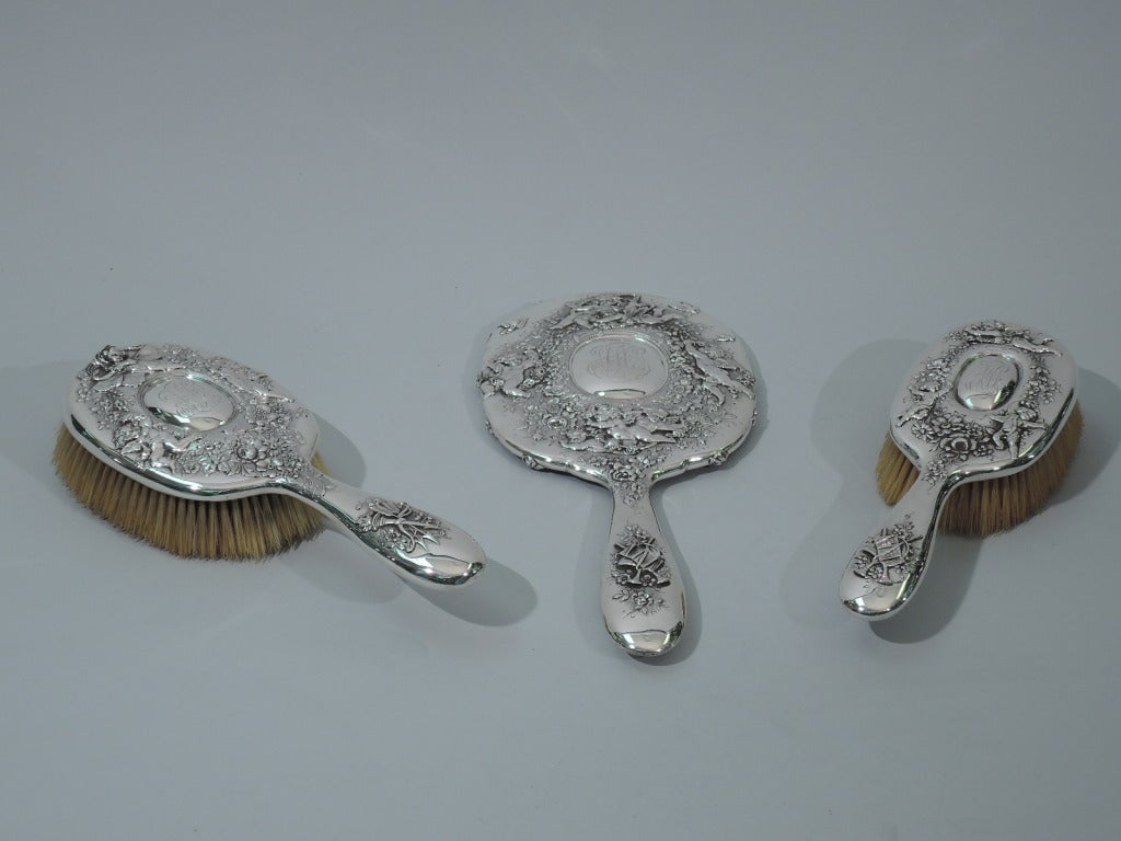 Sterling silver three piece vanity set made by Tiffany & Co. in New York, c1900. This set is comprised of 1 hand mirror and 2 hair brushes.  Mirror: Frame is squarish with curved corners. Handle is curved and tapering. Glass is beveled. Brushes: