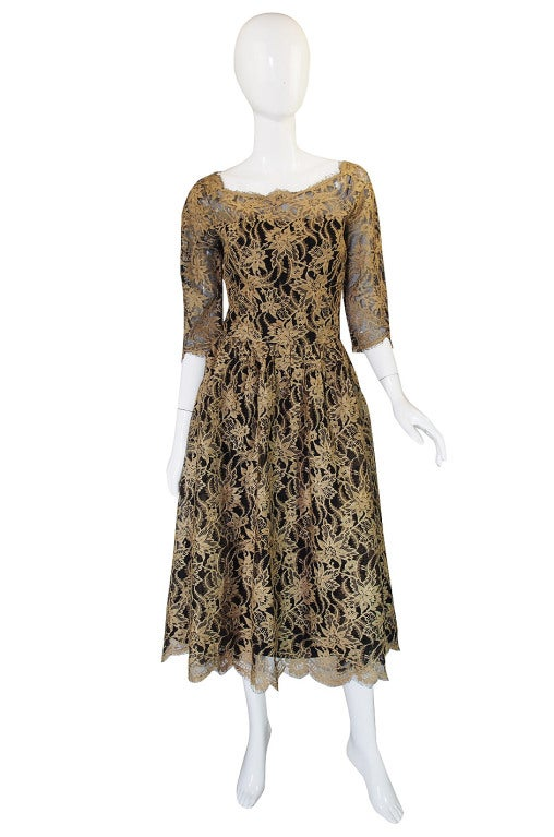 Rare gold toned lace cocktail dress by Jacques Heim. The skirt is cut so that the back is fuller then the front. The underskirt is not cut as full as the top layer of lace so it will not accommodate a really full crinoline. Zip back, inner strapless