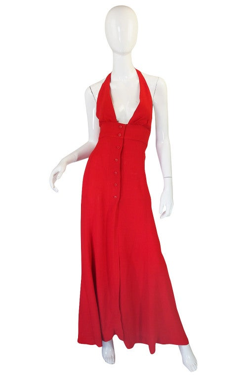 Super price on a classic Ossie Clark. Done in a moss crepe dyed to the perfect red it buttons to close down the front The halter top ties at the back of the neck and the entire back is left bare. It is priced low because there is a small amount of