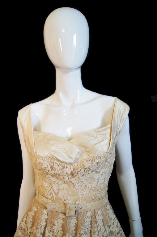 Rare, rare, rare lace couture level dress from the great Jacques Fath. This dress is absolutely beautiful! The lace work is astounding. It is hand made lace on a fine netting all done to create beautiful, feminine flowers. The lace lies over layers