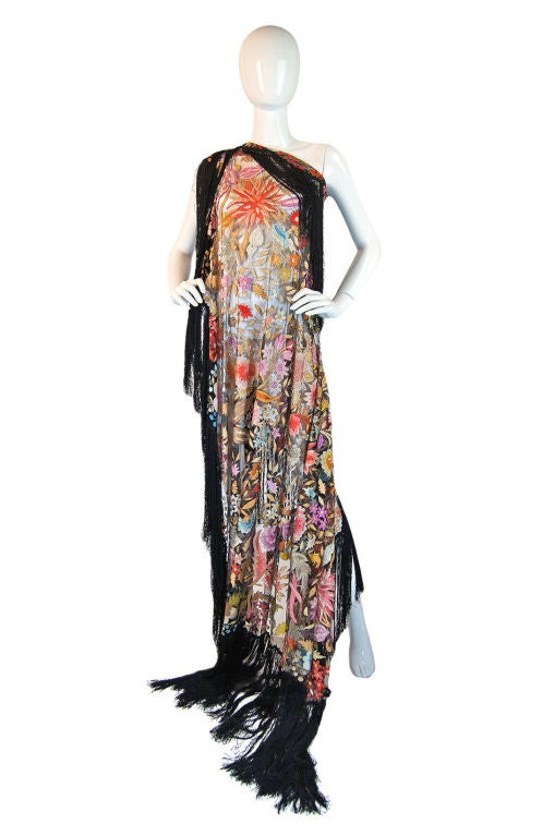 Showstopping, highly collectible 1920s Spanish Floss shawl is a masterpiece and really a work of art. Completely embroidered with silk embroidery threading on a fine black silk netting base, the entire surface is an explosion of color as a riotous