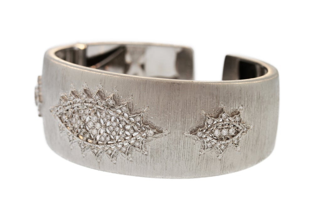 This beautiful cuff bracelet slightly graduated design features three openwork plaques set with round diamonds within a textured gold ground.  Made by the great Italian jewelry firm Buccellati, this bracelet features their iconic textured gold