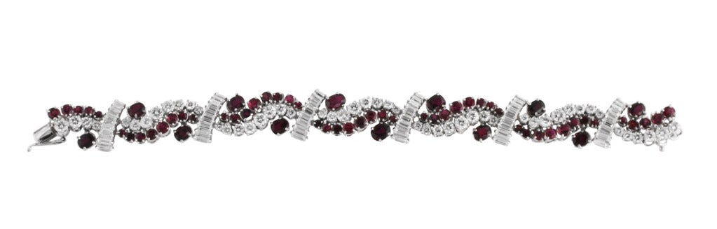 18 karat white gold, ruby and diamond bracelet, designed as a curving bands of rubies and diamonds spaced by diamond lines, set throughout with 50 round and 54 baguette diamonds weighing approximately 9.00 carats, and 50 round and 12 oval rubies