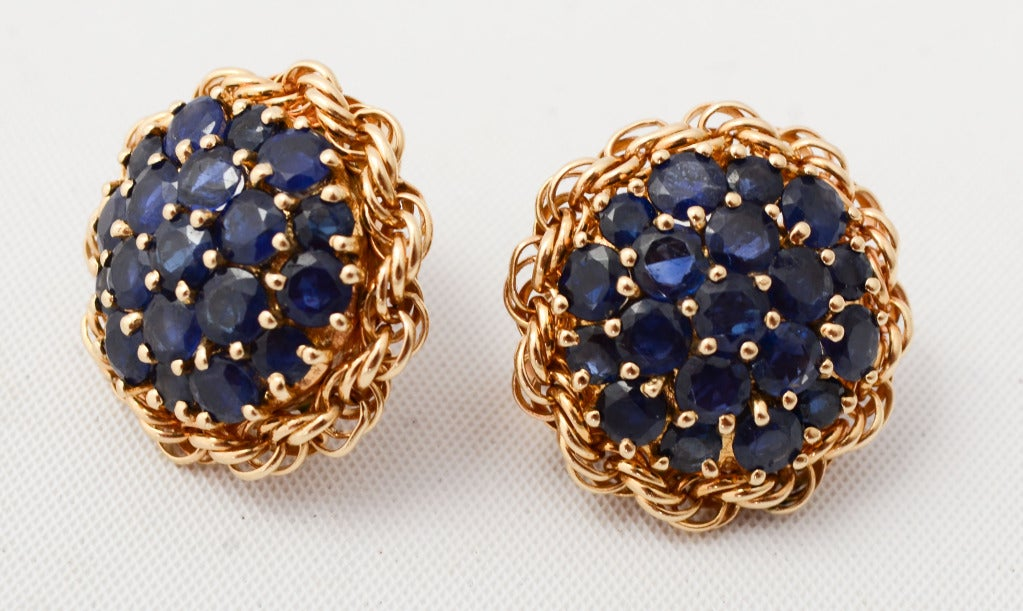 "Cluster earrings with three concentric rows of richly colored sapphires. They are surrounded by an undulating gold rope. 7/8"" in diameter."