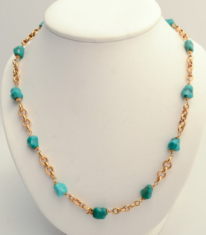"Long 18 karat gold chain necklace with alternating smooth and textured links. The chain measures 41"" long. It has a clasp so it can easily be worn either singly or doubled. The natural chunks of turquoise are richly colored."