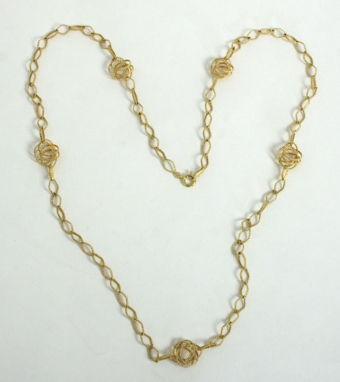 Lozenge shaped links alternate with five interwoven circles in this 35 inch long 14 karat gold necklace made by Uno a-Erre. It has a clasp that allows it to be worn singly or doubled. The elongated and knotted links have different textures.