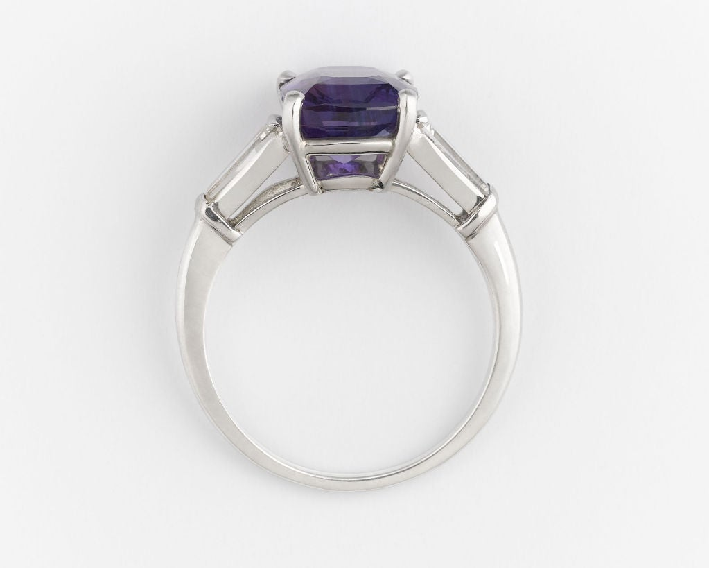This outstanding 4.35 carat purple sapphire displays a translucency and richness of color found in only the most valuable sapphires. The cushion-cut gem is bound by two white diamond baguettes totaling approximately 0.50 carats. Set in a fine