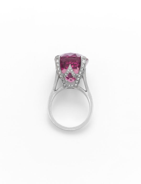 An exquisite, deep pink tourmaline takes center stage in this magnificent cocktail ring. Weighing an incredible 23.65 carats, this rare gem is mounted in a spectacular, 18K white gold basket setting, which boasts .50 carats of diamonds and an