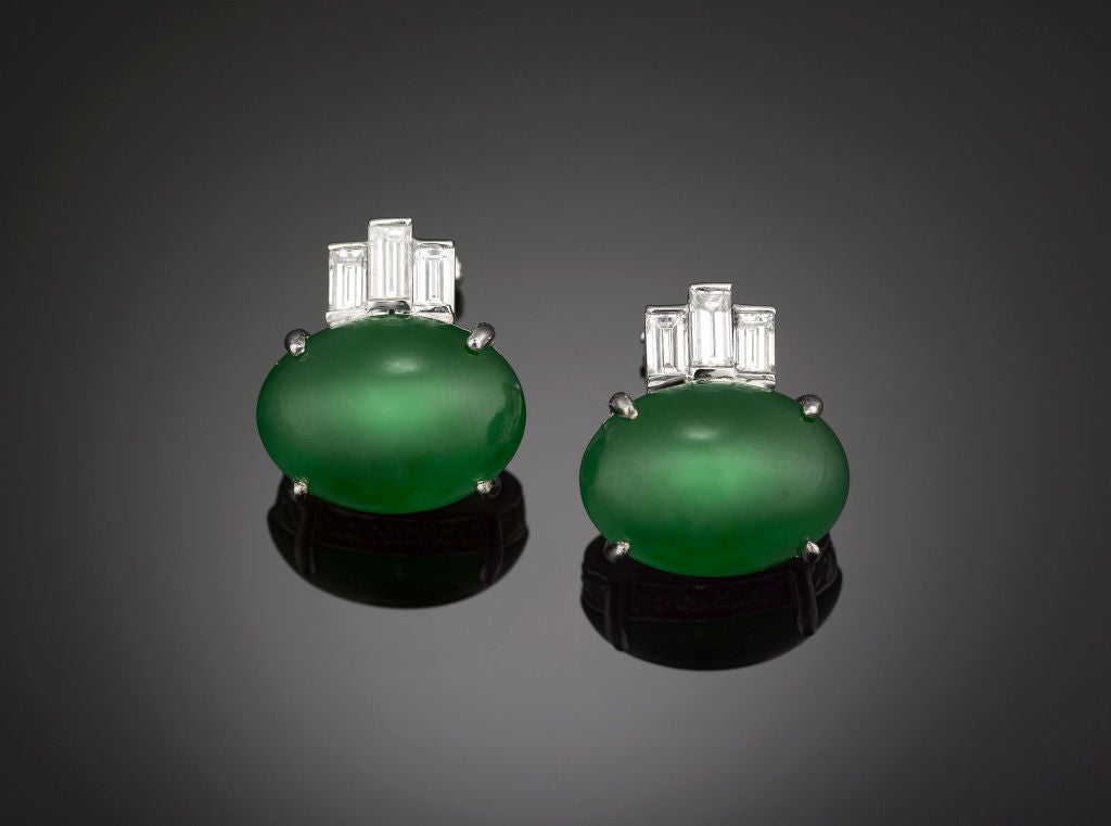 The majesty of Imperial Jadeite is exemplified in this elegant pair of earrings. Two incredible Jadeite cabochons, exhibiting the highly desirable, vivid emerald hue and glasslike translucence, are crowned by three emerald cut diamonds each in an