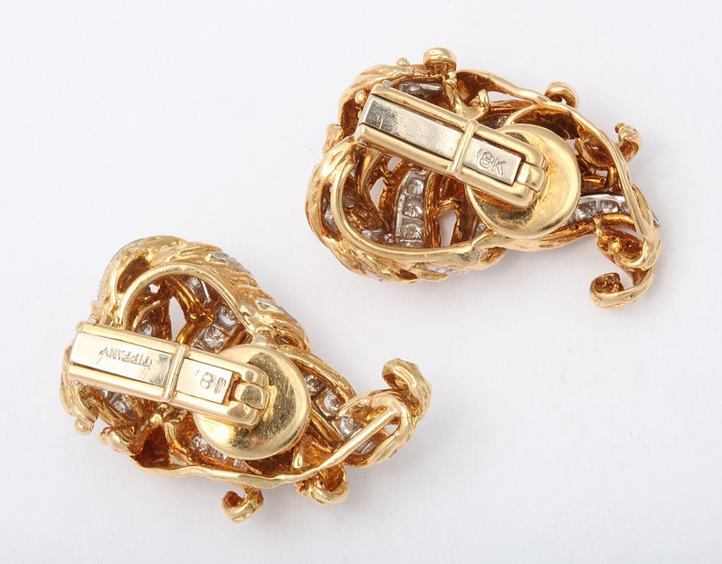 Elegant Tiffany ear clips of rich 18K gold, in a woven ribbon effect with scrolled tips, all set with sparkling diamonds. Tiffany and gold marks. 3/4 x 1 1/4 inches.