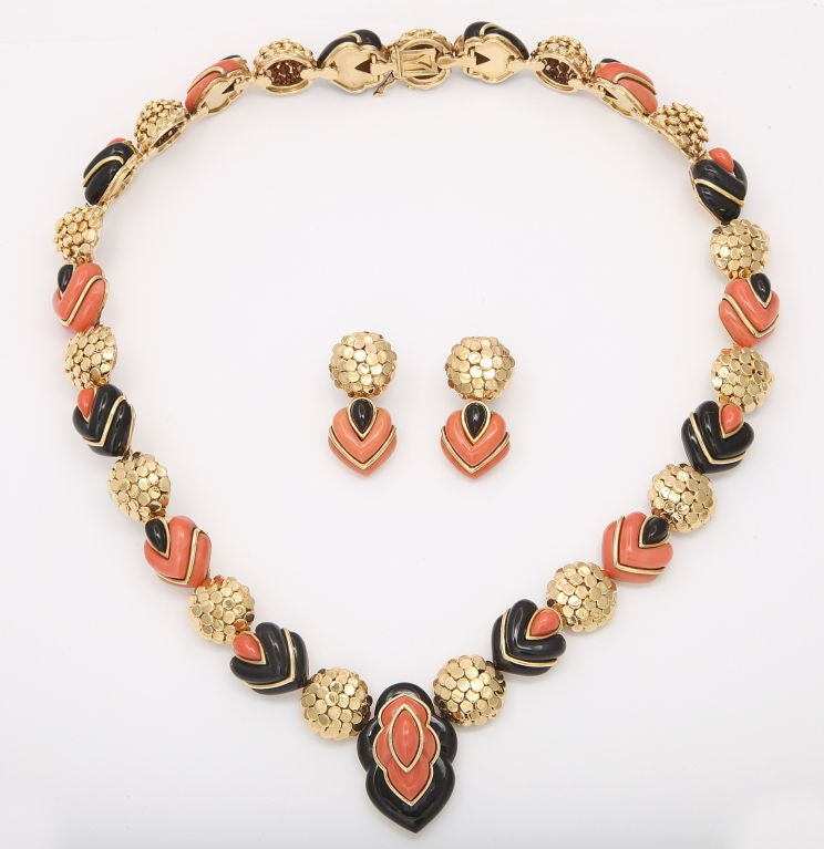 Dramatic necklace and earring set by Wander Paris, featuring hand crafted domed links of 18K gold, connecting alternating elements bulging with carved coral and black jade. Necklace length 19 inches; earring length 1 3/8 inches. Gold marks and
