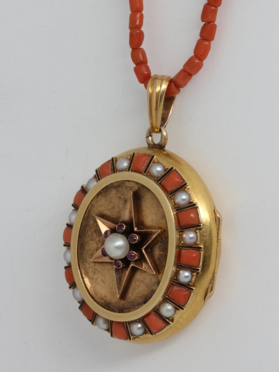 Exceptional 15K yellow gold Victorian locket embellished with 12 alternating coral trapezoid shapes and 12 natural pearls surrounding a concave oval showcasing a 6 pointed star with tiny bezel set cabochons and pearl center. Worn on a matching coral