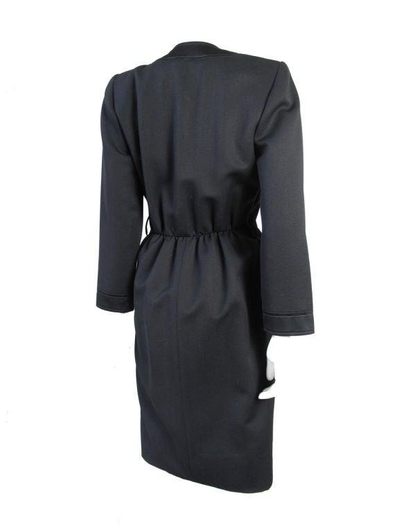 "Yves Saint Laurent black wool gaberdine dress with silk trim and rhinestone buttons. 38"" bust , 27"" waist, 22 1/2"" sleeve, 41 1/2"" length. Condition: Very good, belt missing. Size 36"