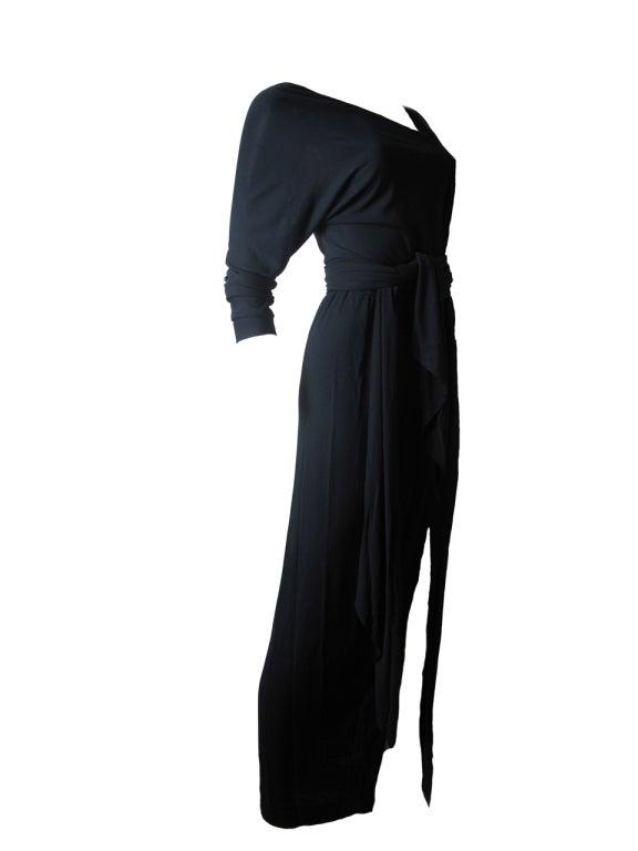 Rare Halston 1970's black silk jersey evening gown.  Large slit in front.  Detachable belt.  Asymmetrical neck.    32
