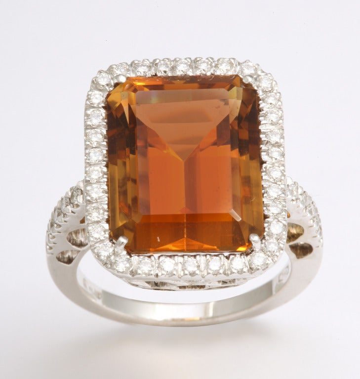 "This beautiful variety of citrine is referred to as ""Madeira"" for it's deep orange-brown color and this emerald cut stone, weighing 11.69cts, is a perfect example.  Delicately mounted with a diamond frame and shank, this ring is destined to attract"