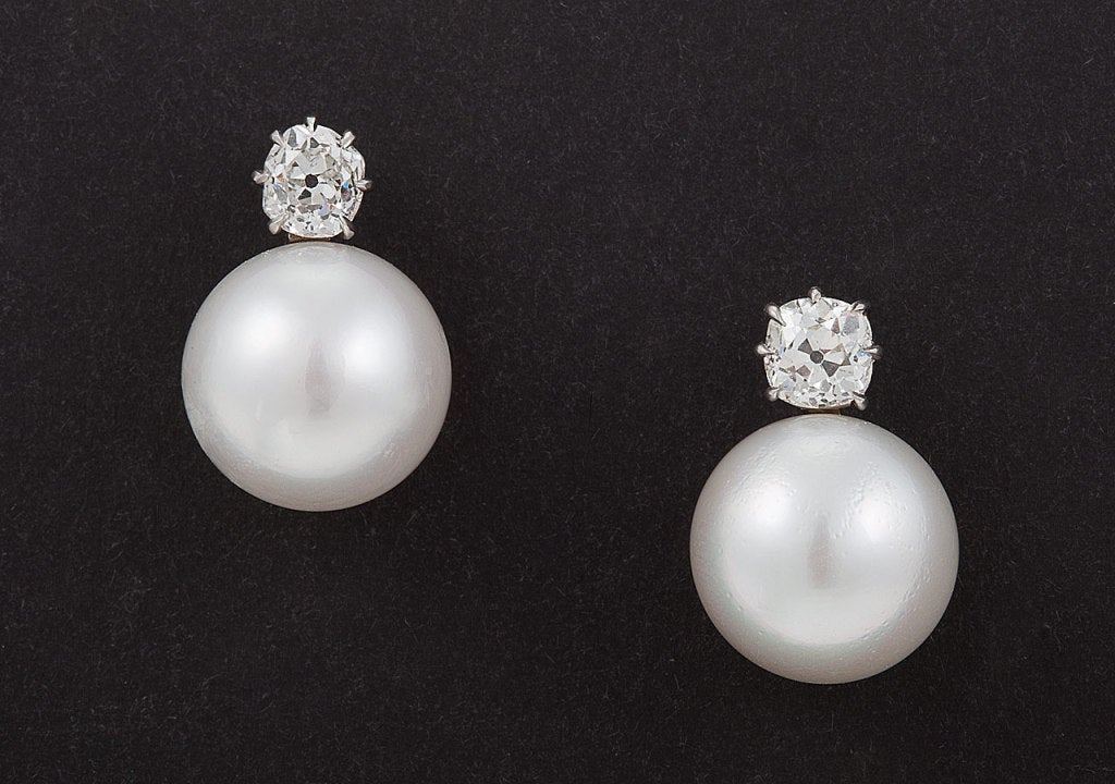 Each earring centers 1 button-shaped South Sea pearl in a platinum mounting suspended from an old mine-cut diamond, circa 1910, color: H-I & I-J, clarity: VS1 & VS2, completed by a post and clutch back. Total diamond weight for the pair is