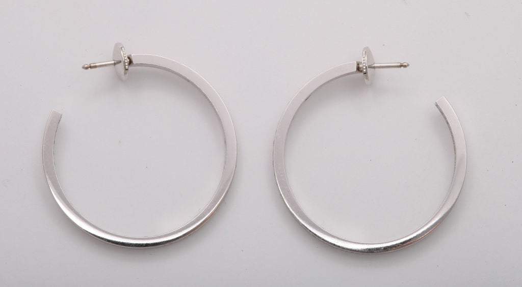 A pair of 18 karat white gold hoop earrings expertly set with precisely matched top quality round diamonds.