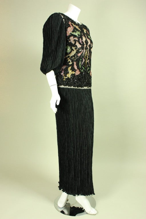 Vintage evening gown from Mary McFadden dates to the 1980's.  The bodice is fully covered with embroidery, sequins, and beads.  Round neck.  3/4-length sleeves with elasticized cuffs.  Black pleated skirt has drop waist.  Center back zipper.  Bodice