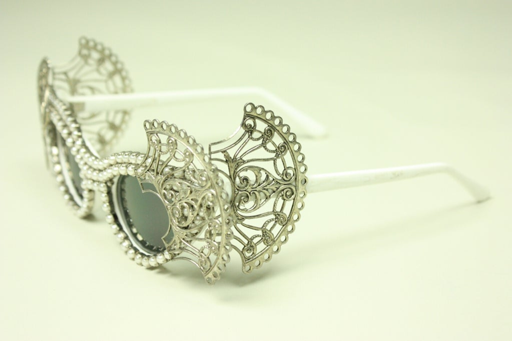 Contemporary cat eye sunglasses from Mercura NYC have pearl and silver-toned filigree detailing.  Gray lenses.  White plastic frames.