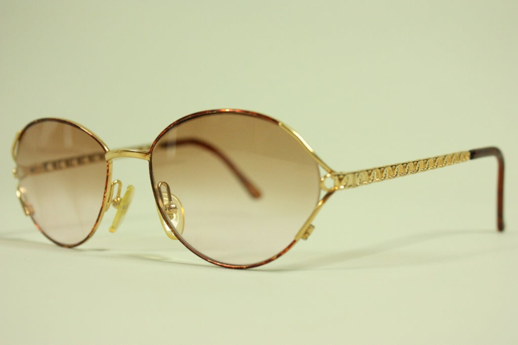 Christian Dior sunglasses date to the 1980's and have gradated plastic lenses. Gold-toned arms have the letters C & D interlocked and repeating.  