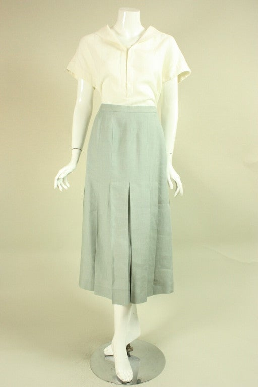 """Vintage Chanel ensemble dates to the 1980's and is made of white & mint green linen.  Short-sleeved blouse has a v-neck and middy collar.  Pleated skirt is mid-calf length and has a zippered closure.  Unlined.  Top Bust: 44"""" Waist: 43"""" Center"""