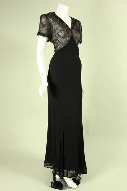 Vintage gown dates to the 1940's and is made of black crepe with a sheer net insert at the bodice and back with metallic floral embroidery.  V-neck.  Short sleeves.  Unlined.  Side zipper.