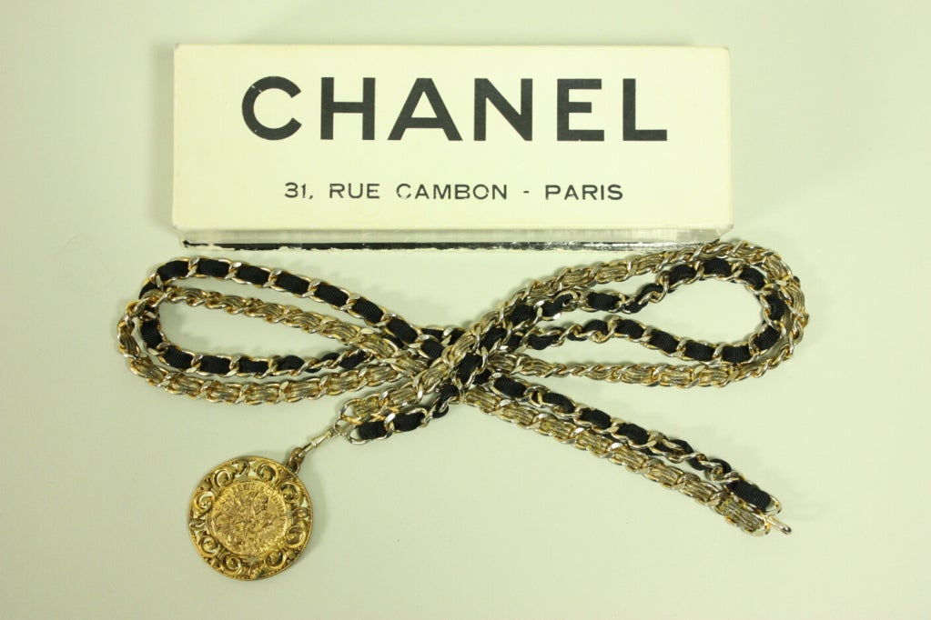 Vintage Chanel belt dates to the 1960's and is made of gold-toned double metal chain.  Gold bullion and black faille are woven through the chain.  Large medallion hangs down from the chain and depicts a man on a horse.  It comes in its original box.