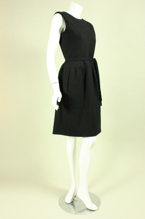 Vintage dress from Norman Norell dates to the 1960's and is made of  black wool crepe.  It has a round neck, drop waisted skirt, and a belt that ties at the natural waist.  Lined.  Center back zipper.