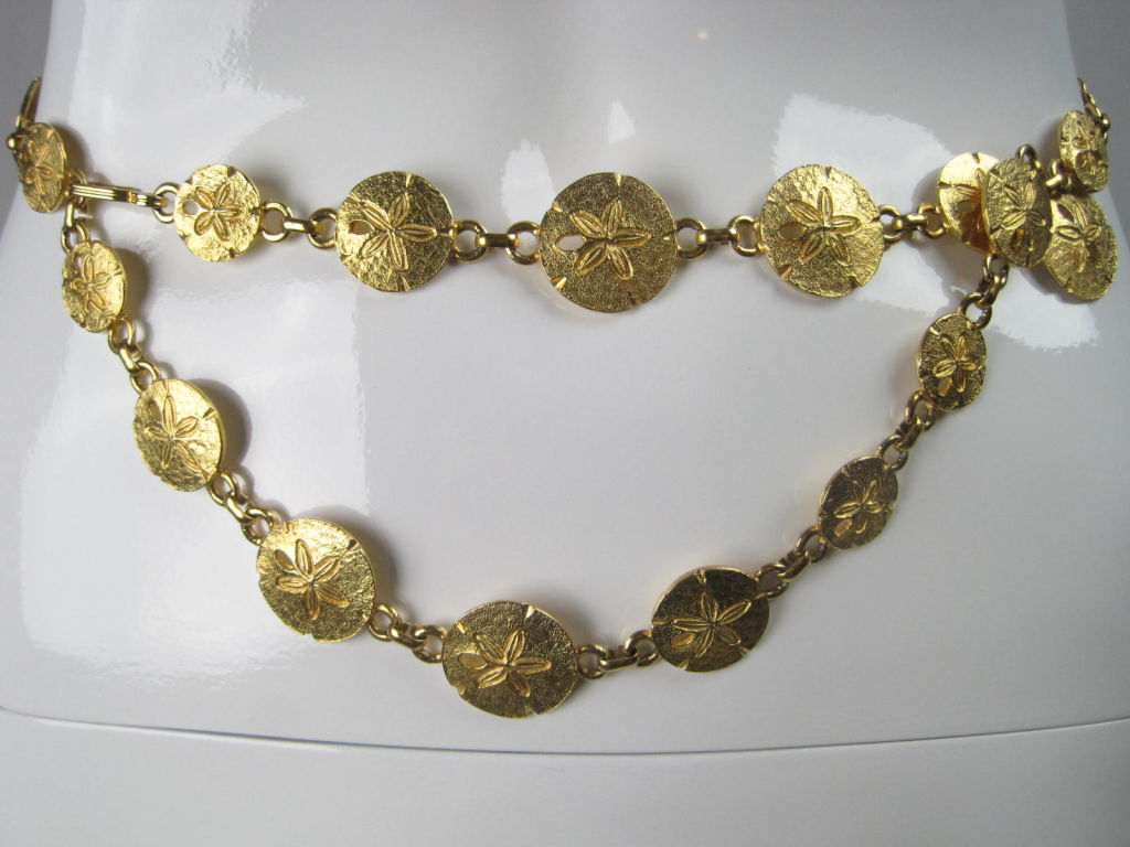 "Mimi Di N belt or necklace circa 1974.  Gold-toned discs of varying sizes are stamped and textured to represent sand dollars.  Held together by chain links.  Each disc is stamped ""Mimi Di N 1974"".  Very versatile accessory.