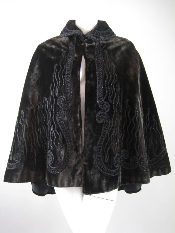 Stunning Victorian-era cape.  Dark chocolate velvet with thick pile has soutache trim and beadwork that resembles flames rising up from the hem.  Double hook and eye closure.  Peter pan collar can be worn turned up or down.  Longer in back.  Lined