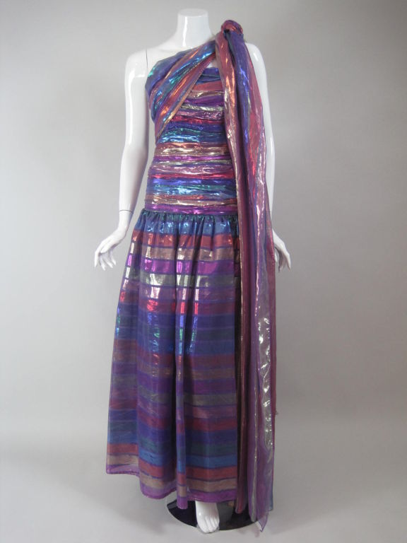 Victor Costa gown is made out of purple lame with multicolored horizontal stripe.  Fitted bodice is ruched throughout.  Drop waist.  Full skirt.  Center back zipper.  Lined.