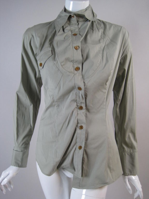Vivienne Westwood blouse with unusual construction.  Made of grey stretch cotton.  Rounded front yoke creates three-dimensional effect.  Single patch pocket at bust is slanted and follows the curve of the yoke.  Button front.  Turn down collar.