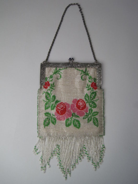 Vintage beaded handbag from the 1920's.  Mini bugle beads are made of white glass and strung neatly in horizontal rows.  Rose motif is made out of pink, red, and green beads.  Silver-toned frame is etched with scrolling detail and has kiss clasp.