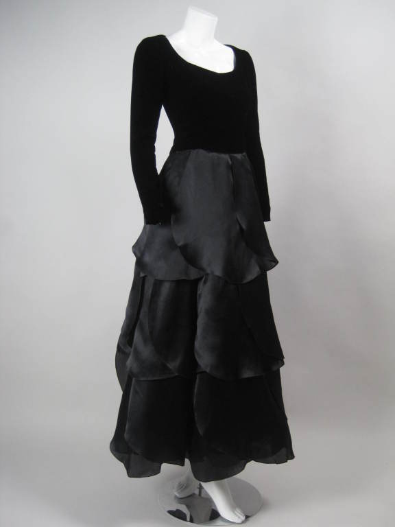 "1980's Carolina Herrera sample gown.  Bodice is made of black velvet with scoop neck and long sleeves with zippered cuffs.  Full skirt is made up of black organza ""petals"".  Center back zipper.  Fully lined.
